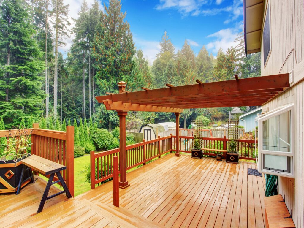 An image of a deck with pergola and bench on the back of a house.
