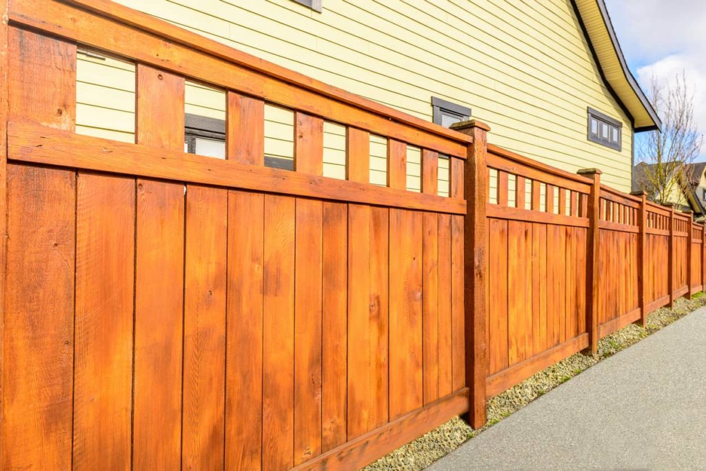 This picture shows a stained wooden fence in front of a house.