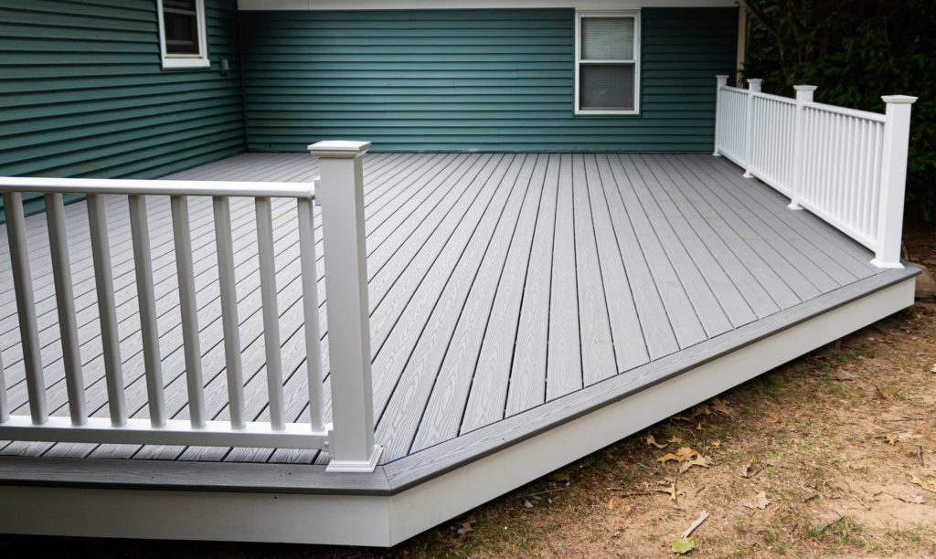 This image shows a white and gray wooden deck for a home's backyard.