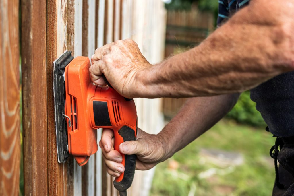 This image shows a man using a power sander to prep a wooden fence for painting.