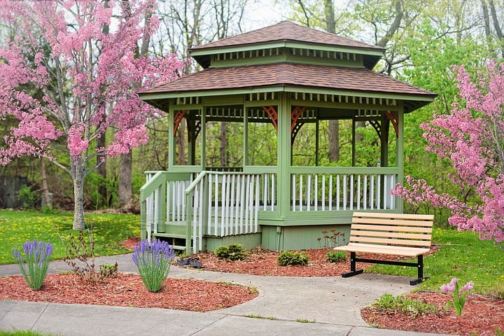 An image of a green and decorative gazebo in a park with pink flowering trees surrounding it.