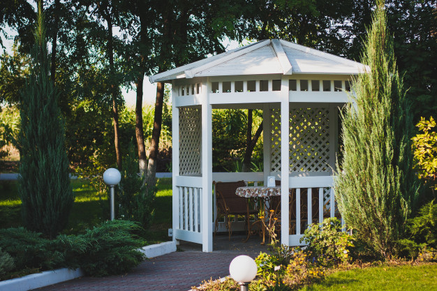 This is an image of a gazebo under a tree in a park.