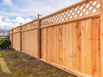 This image shows a light colored wood fence with decorative lattice on the top.