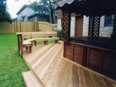 An image of a back deck and porch with bench and jacuzzi.