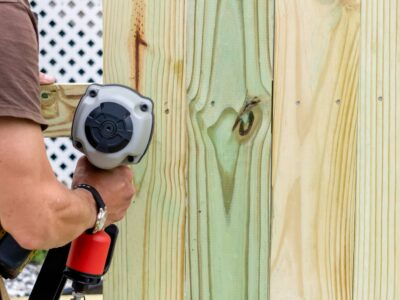 This image shows a fence contractor using a nail gun to install wooden boards for a quality wood fence.